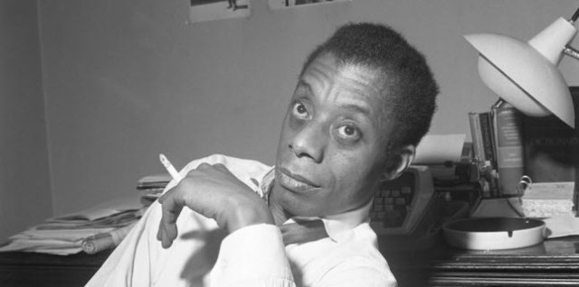 A photographer of author James Baldwin smoking a cigarette.